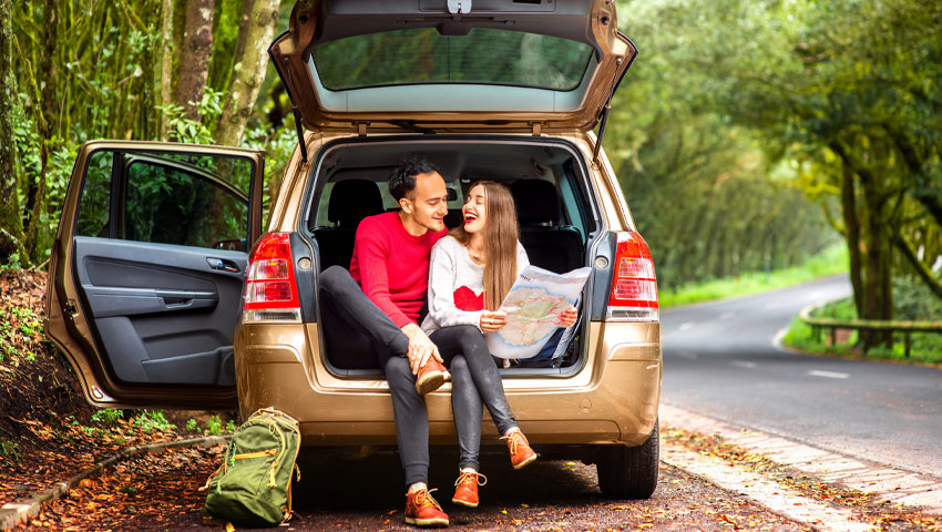Young couple looking at road map sitting in car boot