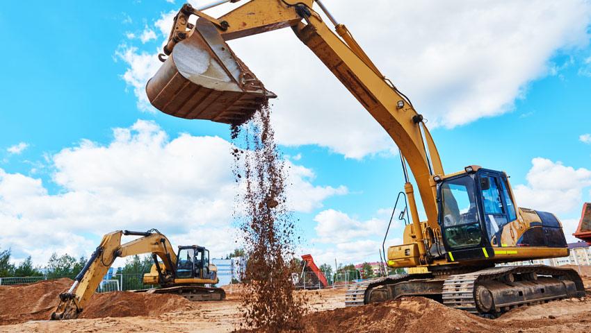 Two yellow excavators moving soil