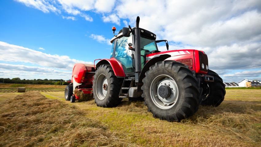 MF tractor with hay baler in paddock