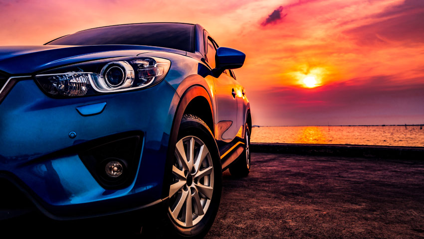 Close up of car bumper bar and headlight with sunset and beach in background